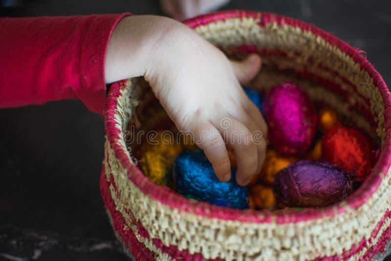 Uovo afferrante della mano dal canestro in pieno delle uova di Pasqua in imballaggio leggero brillanti del cioccolato immagini stock