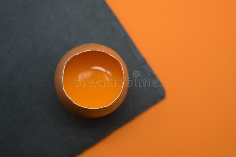 Uovo aperto con il tuorlo sui precedenti arancio immagini stock