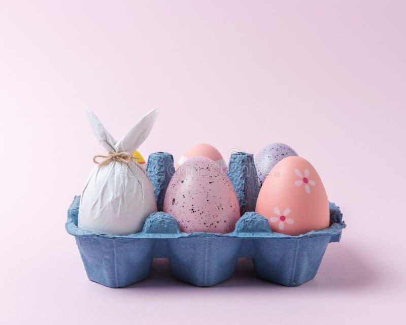 Uovo avvolto in una carta sotto forma di un coniglietto con le uova di Pasqua variopinte in vassoio del cartone Concetto minimo d immagini stock