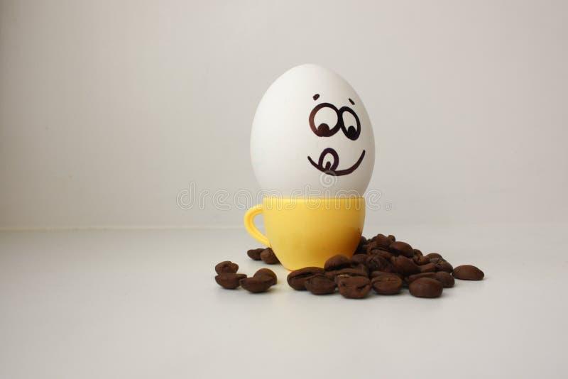 Uovo con un fronte Divertente e sveglio ad una tazza da caffè fotografia stock