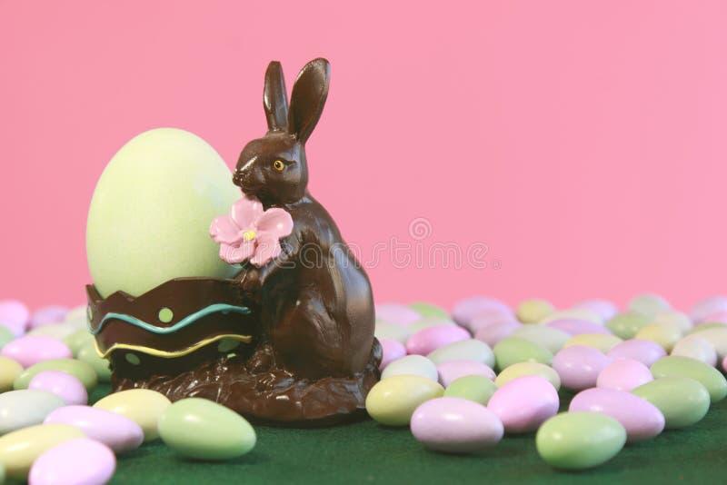 Uovo della holding del coniglietto di pasqua del cioccolato fotografia stock