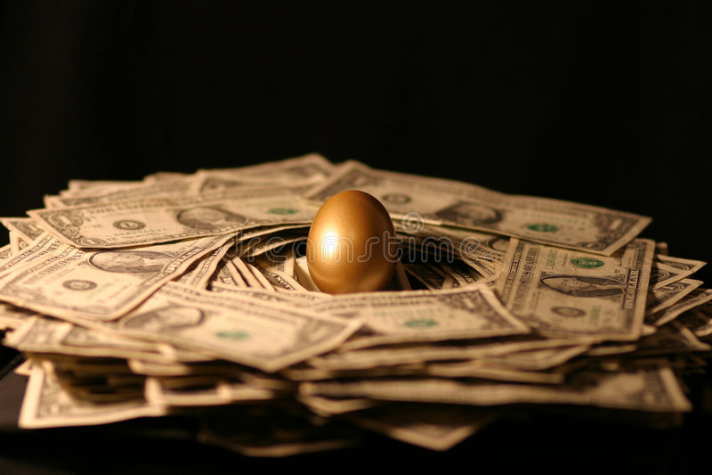 Uovo di nido dorato di soldi immagine stock