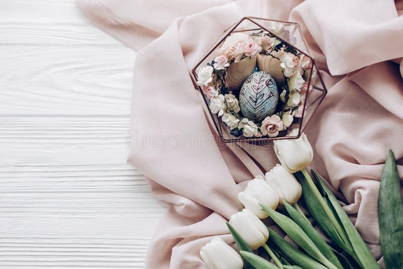 Uovo di Pasqua alla moda con gli ornamenti floreali in nido dei fiori e fotografia stock libera da diritti