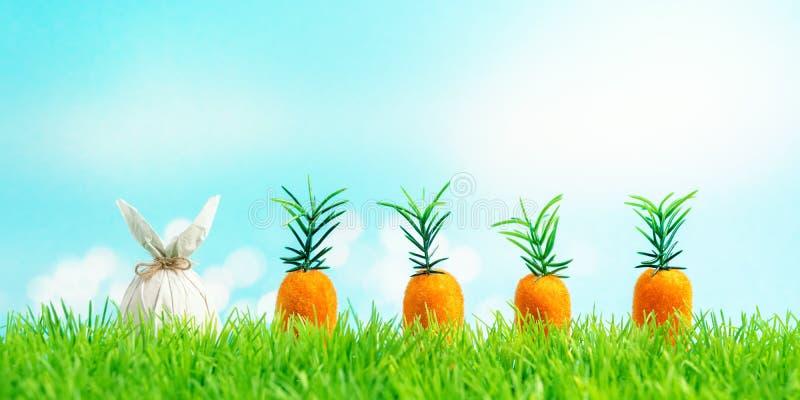 Uovo di Pasqua avvolto in una carta sotto forma di un coniglietto con la carota su erba verde Concetto di feste della primavera immagini stock libere da diritti