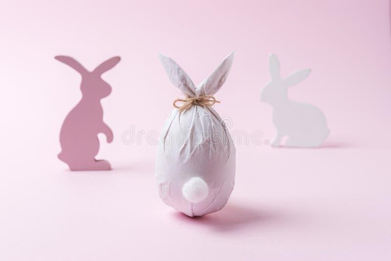 Uovo di Pasqua avvolto in una carta sotto forma di un coniglietto con la decorazione dei coniglietti Concetto minimo di pasqua immagini stock