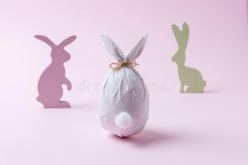 Uovo di Pasqua avvolto in una carta sotto forma di un coniglietto con la decorazione dei coniglietti Concetto minimo di pasqua immagini stock libere da diritti