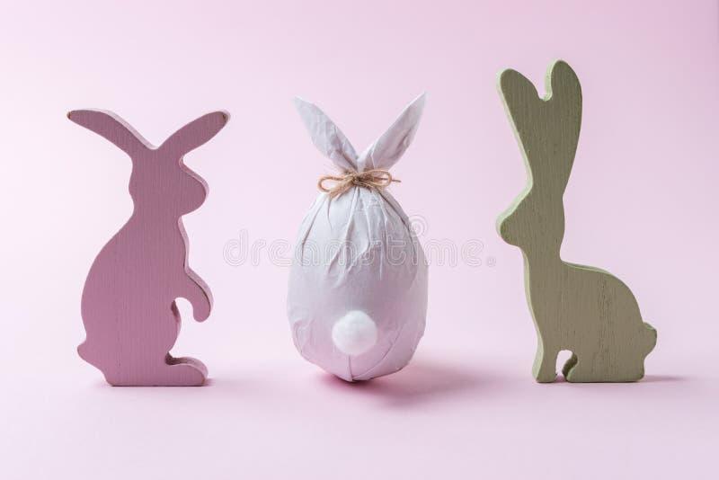 Uovo di Pasqua avvolto in una carta sotto forma di un coniglietto con la decorazione dei coniglietti Concetto minimo di pasqua fotografia stock libera da diritti