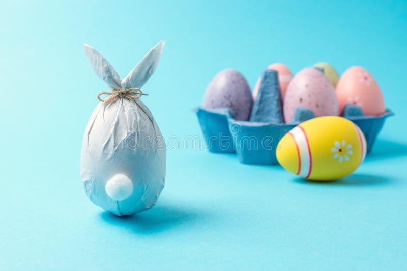 Uovo di Pasqua avvolto in una carta sotto forma di un coniglietto con le uova di Pasqua variopinte Concetto minimo di pasqua fotografia stock libera da diritti