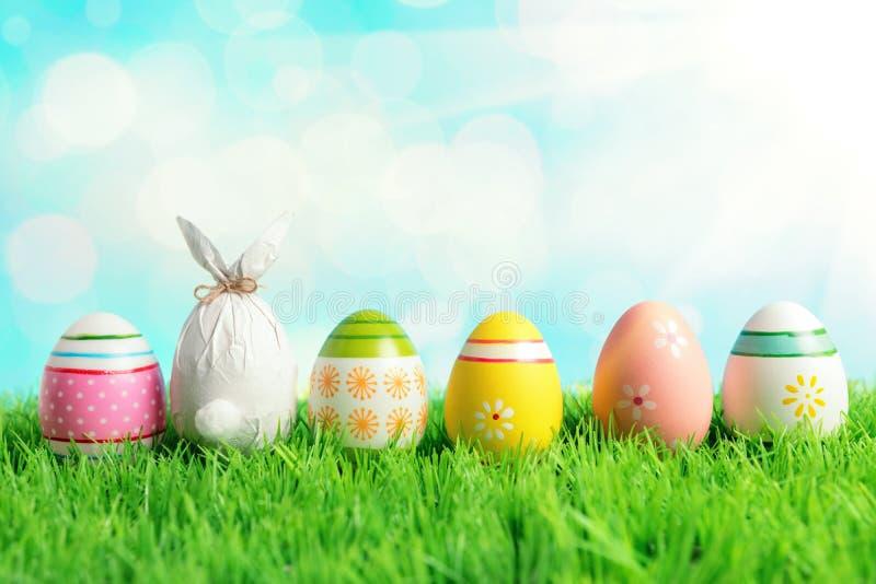 Uovo di Pasqua avvolto in una carta sotto forma di un coniglietto con le uova di Pasqua variopinte su erba verde Concetto di fest fotografie stock