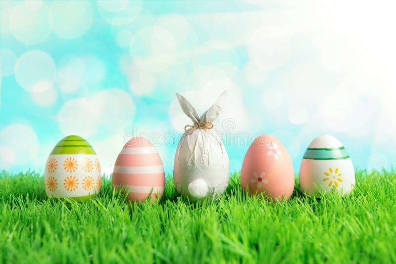 Uovo di Pasqua avvolto in una carta sotto forma di un coniglietto con le uova di Pasqua variopinte su erba verde Concetto di fest fotografia stock