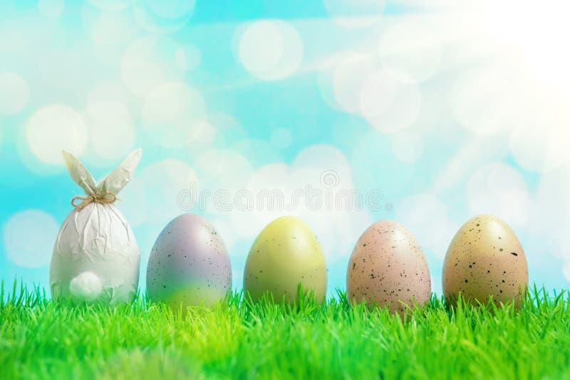 Uovo di Pasqua avvolto in una carta sotto forma di un coniglietto con le uova di Pasqua variopinte su erba verde Concetto di fest immagine stock libera da diritti