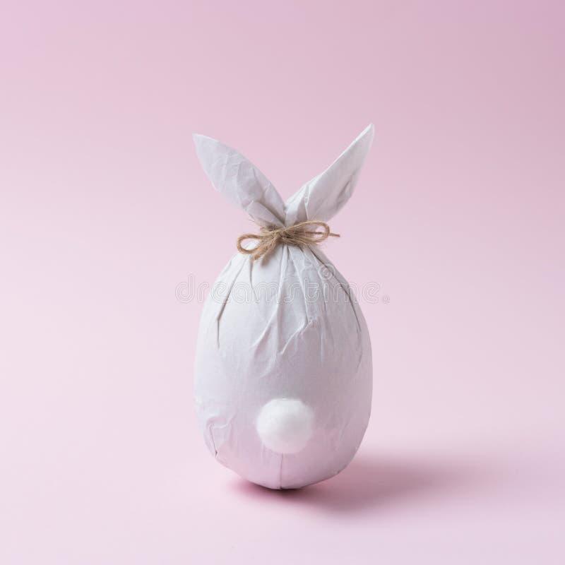 Uovo di Pasqua avvolto in una carta sotto forma di un coniglietto Concetto minimo di pasqua immagini stock