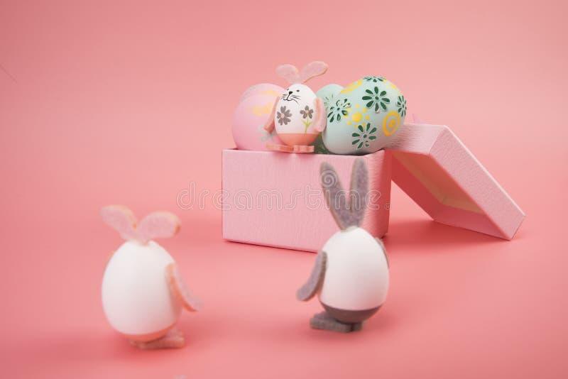 Uovo di Pasqua con il tema rosa nel contenitore di regalo l'uovo è decorato come un coniglietto sveglio che gioca con un altro co immagine stock libera da diritti