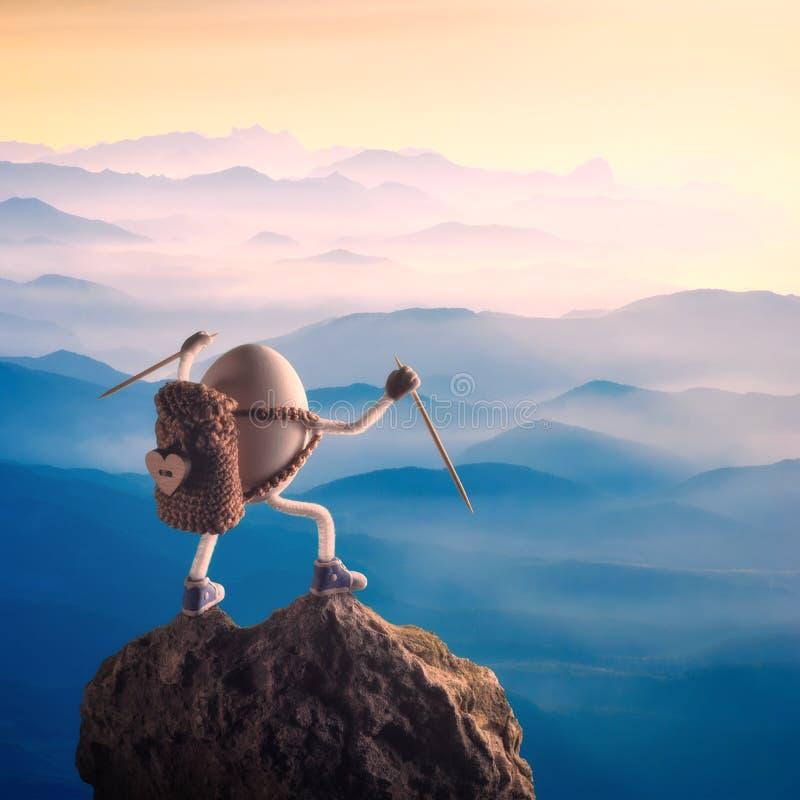 Uovo di Pasqua con le mani sollevate che stanno su una cima della montagna fotografie stock libere da diritti