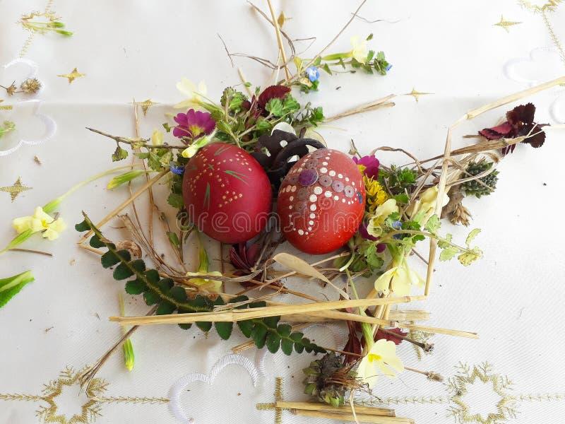 Uovo di Pasqua rosso ornato con i fiori selvaggi e le erbe freschi immagini stock
