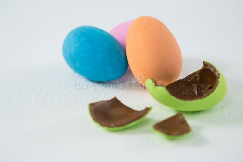 Uovo di Pasqua rotto del cioccolato contro l'uovo di Pasqua di tre cioccolato immagini stock