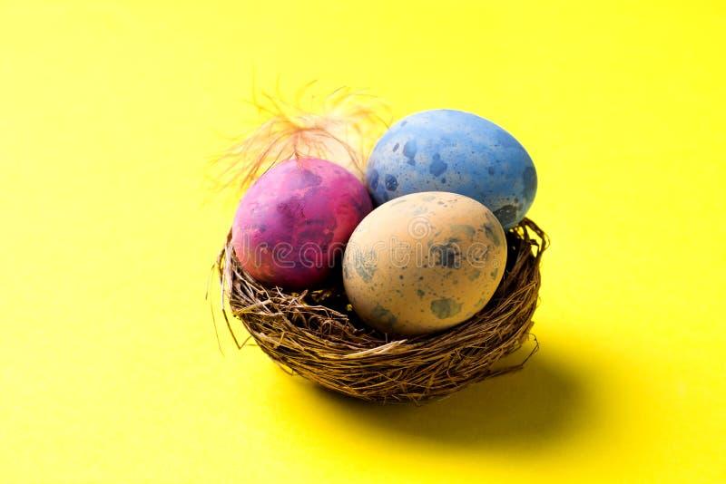 Uovo di Pasqua variopinto nel nido su fondo giallo con lo spazio della copia Priorità bassa di Pasqua minimalism fotografie stock