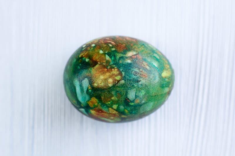 Uovo di Pasqua di verde di Versicolored su sfondo naturale di legno bianco fotografia stock