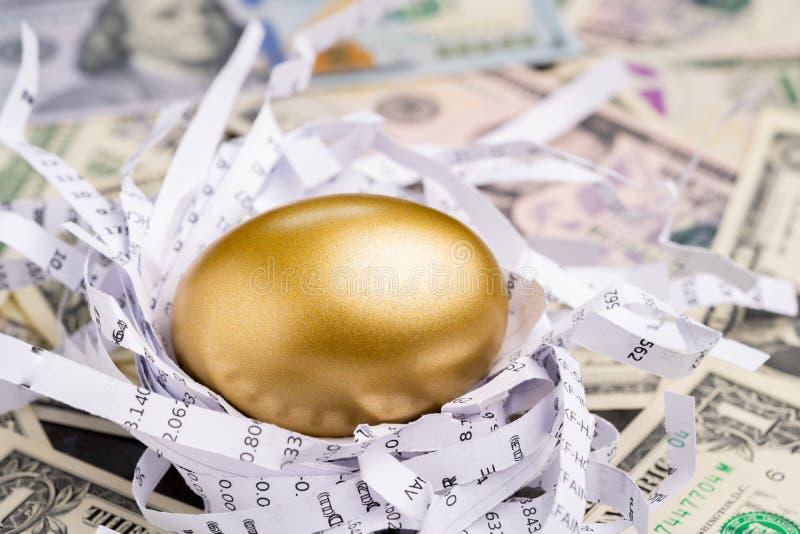 Uovo dorato brillante nel nido della carta con i numeri finanziari sul mucchio della metafora dei soldi della banconota del dolla fotografia stock