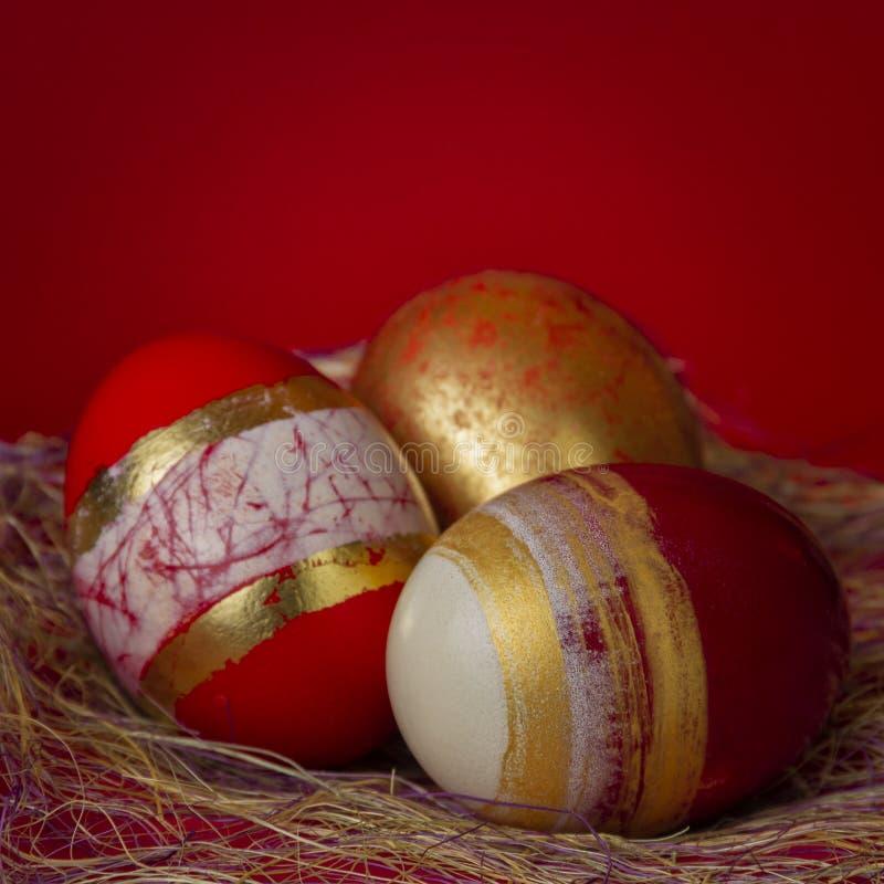 Uovo dorato di concetto di Pasqua di successo su fondo rosso luminoso immagini stock libere da diritti