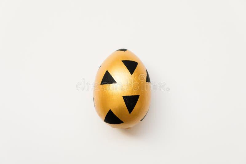 Uovo dorato di Pasqua con il modello nero triangolare isolato su fondo bianco Concetto minimo di pasqua Carta di pasqua felice co fotografia stock libera da diritti