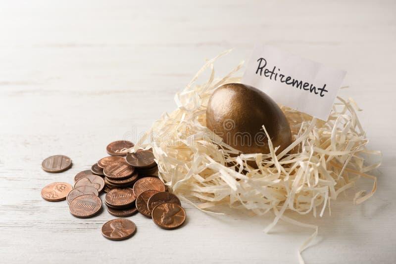 Uovo e carta dorati con la parola PENSIONAMENTO in nido vicino alle monete su fondo di legno immagini stock libere da diritti
