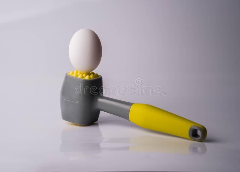 Uovo e martello sulla tavola Simbolo di forza, di forza e di qualche cosa di dure ed infrangibili Concetto di fragilità e di pote fotografie stock libere da diritti