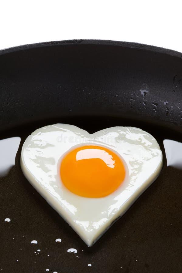 Uovo a forma di del cuore in una vaschetta di frittura fotografia stock