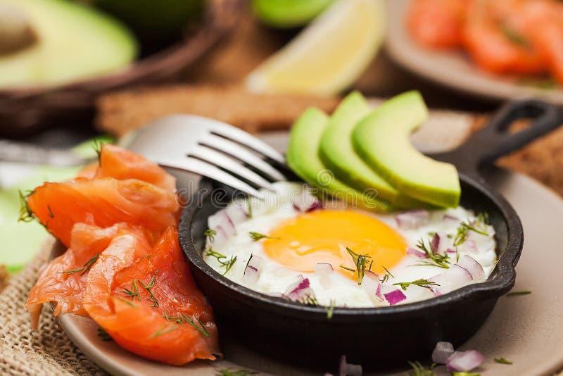 Uovo fritto, avocado e salmone affumicato in padella immagini stock
