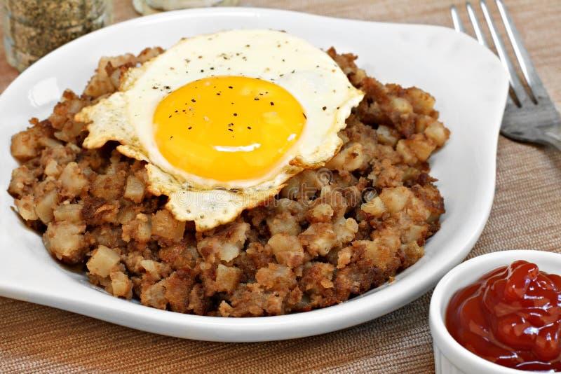 Uovo fritto in cima al hash del manzo di arrosto. fotografia stock libera da diritti