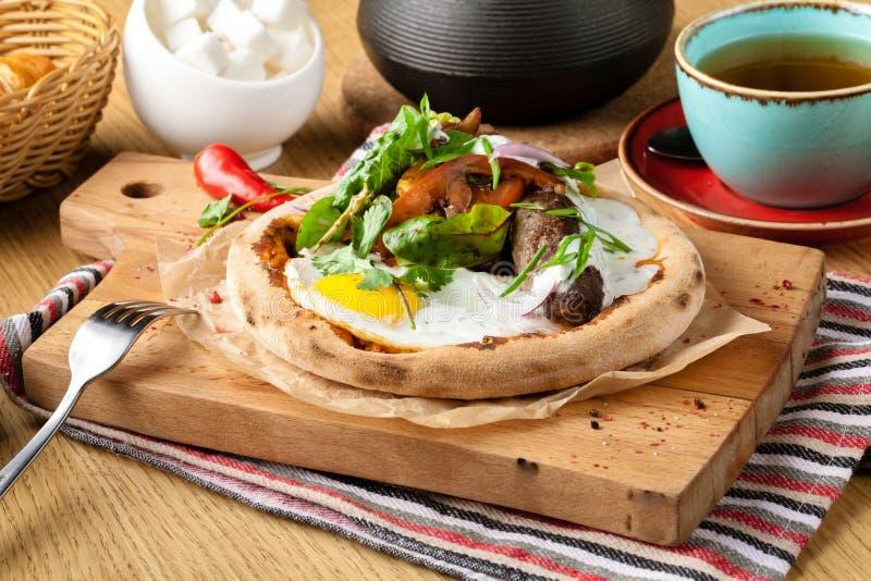 Uovo fritto dell'insieme della prima colazione, insalata, pollo affumicato della salsiccia, prosciutto, pane sulla tavola di legn fotografia stock