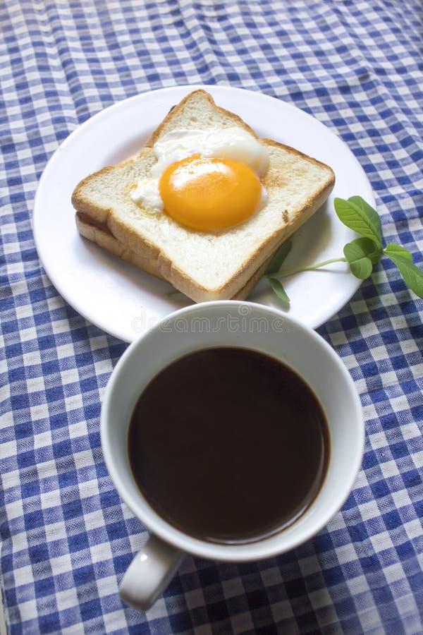 Uovo fritto su pane tostato e su caffè nero in un vetro fotografie stock libere da diritti
