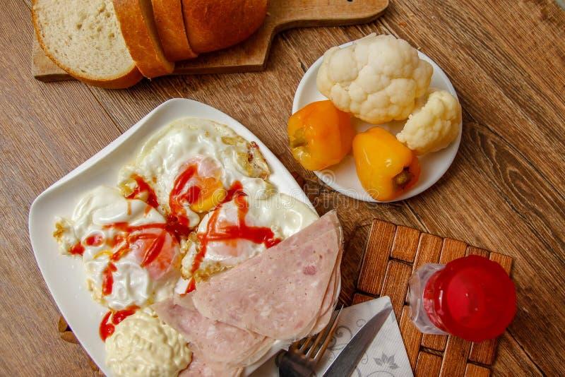 Uovo fritto sul piatto bianco con il prosciutto, il ketchup e la maionese fotografie stock