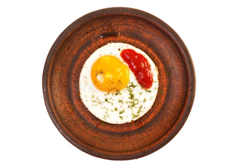 Uovo fritto sul piatto ceramico con ketchup ed aneto Vista superiore, isolata su fondo bianco fotografie stock libere da diritti