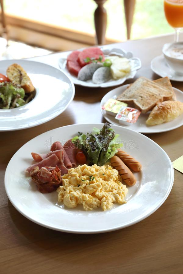 Uovo rimescolato prima colazione con la salsiccia e l'insalata di bacon su fondo di legno fotografia stock libera da diritti