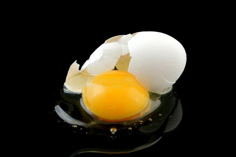 Uovo rotto sul nero fotografia stock
