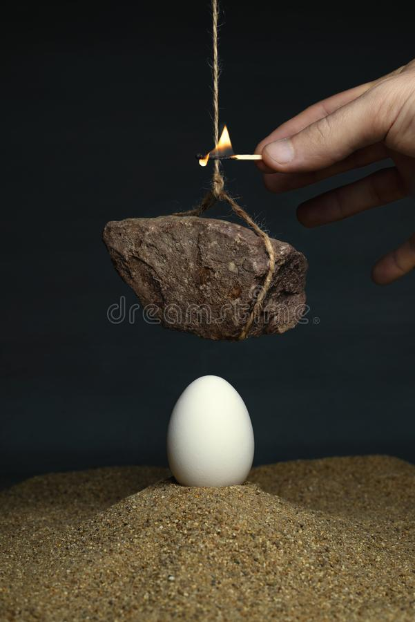 Uovo sotto una pietra che appende su una corda fotografia stock libera da diritti