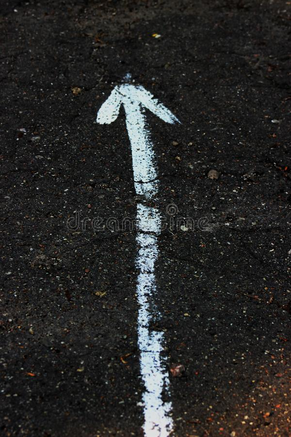 The up arrow on the asphalt is drawn in white paint stock photography