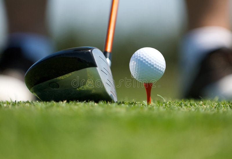 Up close image of a golf ball on tee with club. An up close image of a golf club next to a ball on tee royalty free stock photography