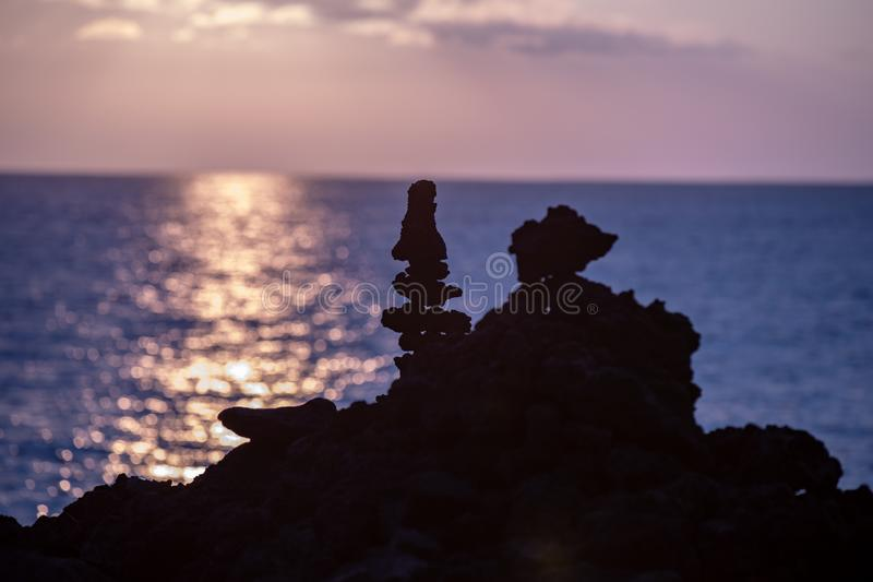 Up close view of silhouettes of tall lava rock formations against sunset over Pacific Ocean stock image