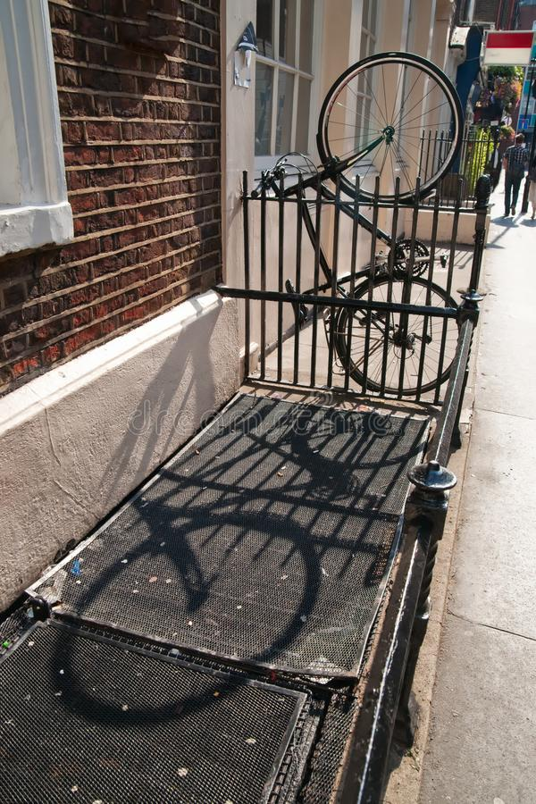 Up ended bicycle casts a shadow on the iron grid stock photography