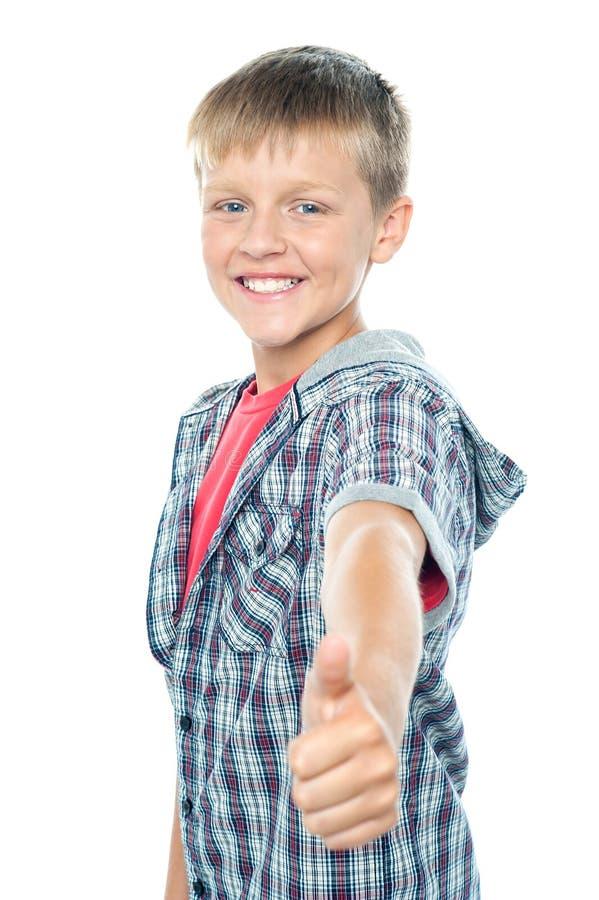Up göra en gest tum för stilig ung pojke tecknet arkivfoto
