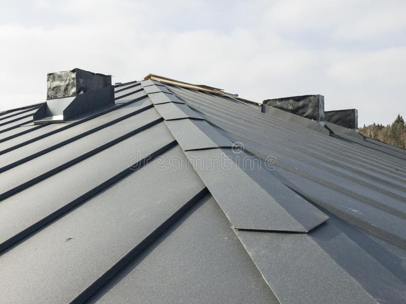 Close up view of grey folding roof and chimney on waterproofing layer of house under construction. Up  of grey  roof and chimney on waterproofing layer of house royalty free stock photo