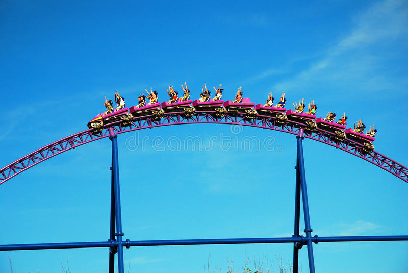 Up and Over. Thrill seekers reach for the sky as their rollercoaster ride crests over a hill stock image