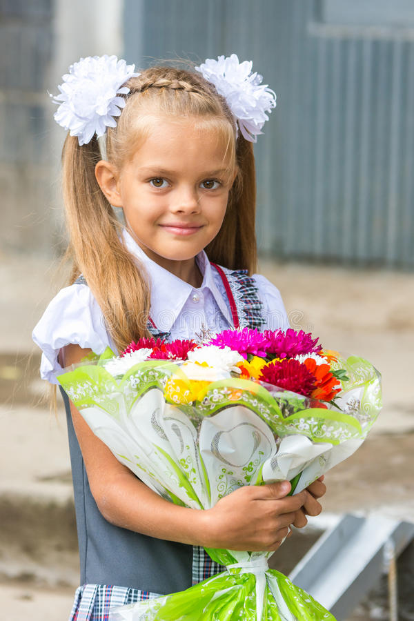 Up portrait of a seven-year school girl with bouquet of flowers stock photography