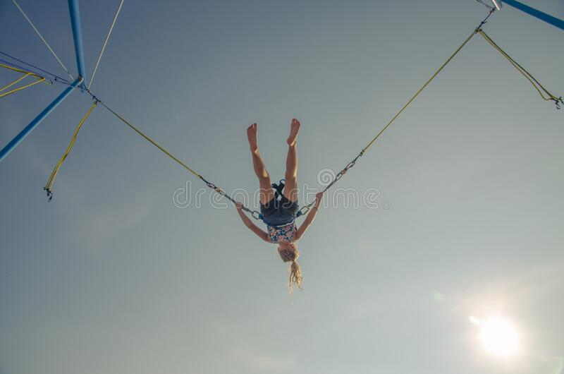 Up side down. Active little young teen girl jumping in trampoline high into the blue sky safed with  elastic safety belt stock images