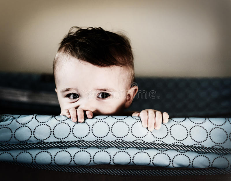 Up to no Good - Retro. A small toddler boy peers over the top of his crib or playpen with a mischievous look. Processed for an aged vintage retro look stock photo