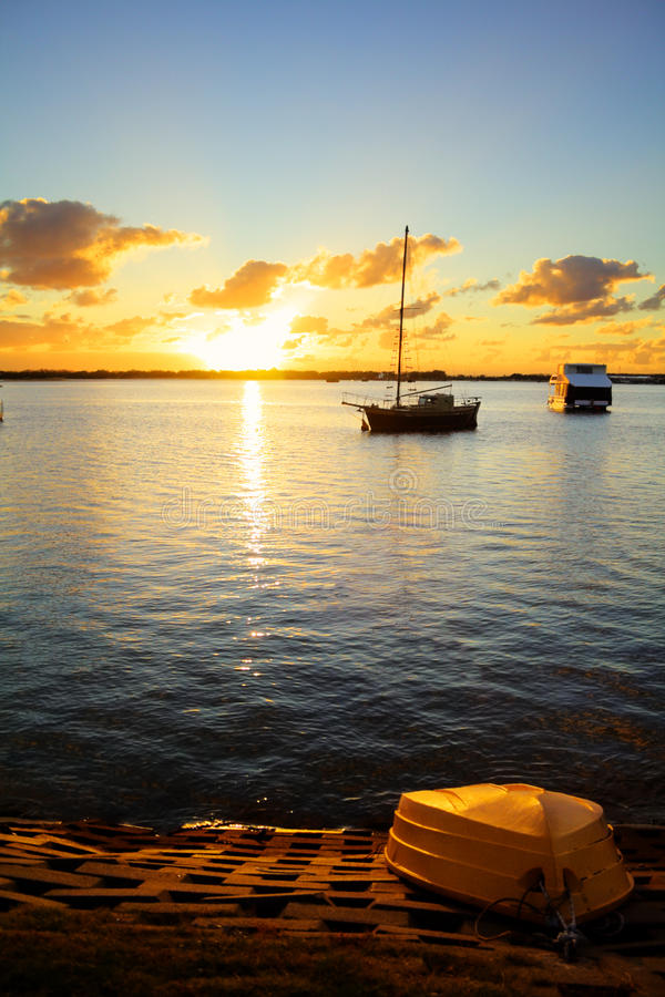 Up Turned Dinghy. On the shore as the sun rises over the water stock photos