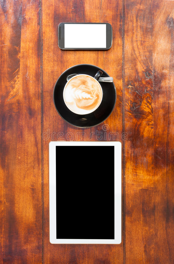 Up view of tablet smartphone and cup of coffee. On wooden terrace table with copy space stock image