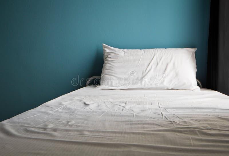 Upaćkany biały łóżko i jeden poduszka, bława ściana zdjęcie royalty free